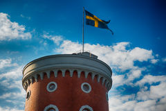 Swedish banner on a tower. A Swedish banner towards blue skyes at the top of a military tower stock photography
