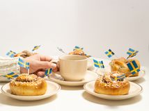 Free Swedish Cinnamon Buns Kanelbullar And Coffee Cup In Hand On The White Wooden Table. Swedish Flags. Stock Photos - 164359383