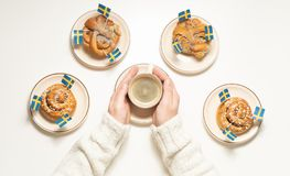 Free Swedish Cinnamon Buns Kanelbullar And Coffee Cup In Hands On The White Wooden Table. Swedish Flags. Coffee Break Fika Concept. Stock Photos - 164359193