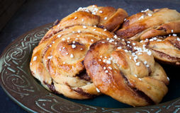 Swedish cinnamon buns. Traditional Swedish cinnamon buns served on a rustic plate. A very popular snack throughout Scandinavia known as Fika when taken with a Stock Photos
