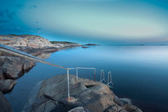 Swedish coastline. A railing leading to a small set of stairs going in to the water Royalty Free Stock Images