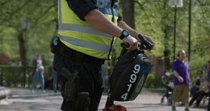 Swedish cop on a segway using his walkie talkie in Mariatorget park. People hanging out on benches and walking in the background. Slow motion shot in 4K stock video footage