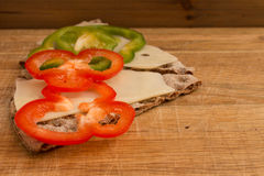 Swedish crispbread with cheese and pepper slices. Closeup of Swedish crispbread with slices of hard cheese and pepper on wood, studio isolated Stock Image