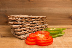 Swedish crispbread and pepper slices. Closeup of Swedish crispbread and slices of pepper on wood, studio isolated Stock Photos