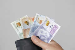 Swedish currency in a black wallet and a hand Stock Photo