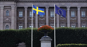Swedish and EU Flag in front of the Swedish Parliament. The Swedish Flag next to The Flag of the European Union with the Swedish Parliament (Riksdag) in the Stock Photo
