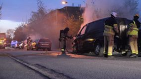 Swedish fire department putting out car fire. Swedish fire department putting out fire right next to a school in poorest parts of Malmo city. Arson is now a