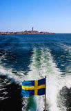 Swedish flag. Swedish flag on a boat, waves after the boat, a lighthouse in the horizon Royalty Free Stock Photos