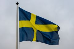 The Swedish flag waving in the wind. The Swedish flag or banner on a flag pole waving in the wind against a white sky Stock Photos