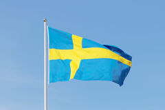 Swedish flag, blue and a yellow cross, blue sky Royalty Free Stock Photography