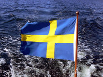 Swedish flag on boat. Swedish flag waving in the wind, sea water in the background stock image