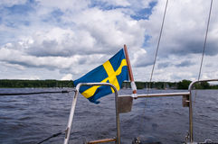Swedish Flag on Boat. A Swedish flag waving in the wind at the boat stern Royalty Free Stock Photography