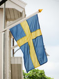 Swedish flag floating. From a wooden building Royalty Free Stock Images