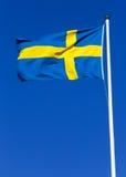 Swedish flag. Hoisted against a clear blue sky Royalty Free Stock Photography
