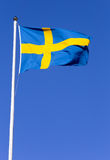 Swedish flag. Hoisted on a flagpole against a blue sky Royalty Free Stock Images