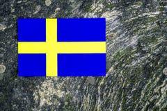 Swedish flag on mossy rock background stock photos