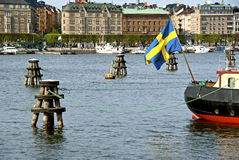 Swedish flag. Nybroviken in Stockholm with boats and the swedish flag and buildings in background Stock Photo
