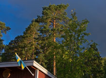 Swedish flag on red cabin Stock Photos