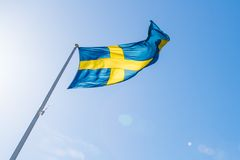 Swedish Flag Waving Against a Blue Sky. Swedish Flag Waving in the Midday Sun and Flare with Blue Sky in the Background Stock Image