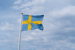 Swedish flag waving. Flag of Sweden in the sky Royalty Free Stock Images