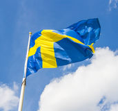 Swedish flag waving in the wind on a blue sky. Background Stock Photo