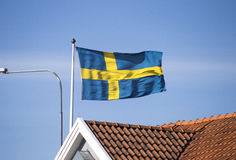 The Swedish flag waving in the wind. The Swedish flag roams in the wind over the roof rack Stock Photography