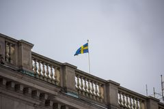 Swedish flag waving in the wind. Skandinavian Sweden flag on grey sky. Stocholm Royalty Free Stock Photography