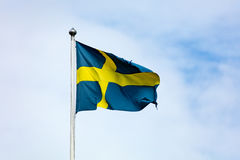 Swedish flag waving in the wind. Swedish flag with a torn edge waving in the wind. Partially cloudy sky Royalty Free Stock Photos