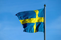 The Swedish flag. The Swedish yellow and blue flag blowing in the wind against a blue summer sky from a flagstaff in Uppland, Sweden royalty free stock image