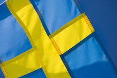 Sweden's yellow and blue flag. Swedish flag, yellow and blue, a symbol of Sweden with a blue sky in the background Royalty Free Stock Photography