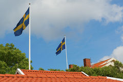 Swedish flags. Two Swedish flags towards a blue sky over red tilded roofs Royalty Free Stock Photos