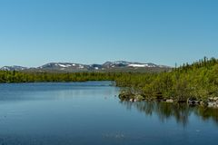Swedish highlands in summer sunshine. View of the Swedish highlands or fjeld world with mountain peaks and a small lake, on a beautiful summer day with blue sky royalty free stock photo