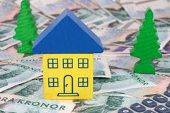 Swedish House. A house in Swedish colours sitting on SEK notes, with a calculator and trees Royalty Free Stock Image