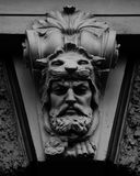 The swedish hunter. Shot in black and white, detail on an sculpture representing an ancient hunter placed on the facade of this historic building, set in Royalty Free Stock Photo