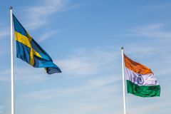 Swedish and Indian Flag with a Blue Sky Royalty Free Stock Photos