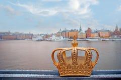 Swedish kingdom golden crown. Golden crown on Skeppsholmen bridge, symbol of the Kingdom of Sweden, with Stockholm Old Town in background Stock Photos