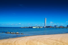 Swedish Malmo West Harbor Area Cityscape with Turning Torso. MALMO, SWEDEN - JUNE 26, 2015: Sandy Beach and Malmo West Harbor Area Cityscape with Turning Torso Royalty Free Stock Photography