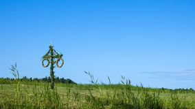A Swedish maypole on a green summer meadow.  stock photo