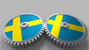 Swedish national project. Flags of Sweden on moving cogwheels. Conceptual 3D rendering. Swedish national project. Flags of Sweden on moving cogwheels. Conceptual Royalty Free Stock Photography