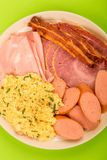 Swedish or Norwegian Style Scrambled Eggs Sausage Bacon and Ham. Breakfast Against A Green Background Stock Photography