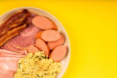 Swedish or Norwegian Style Scrambled Eggs Sausage Bacon and Ham. Breakfast Against A Yellow Background Royalty Free Stock Photography