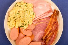 Swedish or Norwegian style scrambled eggs sausage bacon and ham. Breakfast against a blue or purple background Royalty Free Stock Photo
