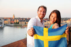Swedish people showing Sweden flag in Stockholm. Swedish people holding Sweden flag in Stockholm. Candid fresh Scandinavian men and Asian women looking at old Stock Photography