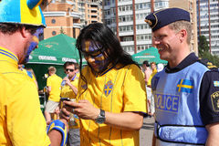 Swedish policeman and football fans Stock Photos