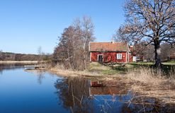 Swedish red  house at a lake. Stock Photos