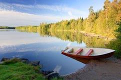 Swedish september in lake scenery. Idyllic september lake landscape with red rowboat Stock Photography