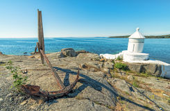 Swedish summer sea coast view with anchor and lighthouse Royalty Free Stock Image
