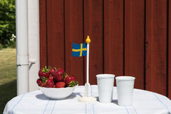 Swedish summer table. With fresh strawberries, flag and two mugs by a red plank wall in a garden royalty free stock photography