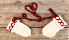 Swedish Traditional handicraft lovikka mittens on wooden background and heart shaped yarn string. Knitted mittens in wool royalty free stock images