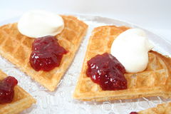 Swedish waffle with jam and cream. Waffle in pieces with raspberry jam and cream Royalty Free Stock Image